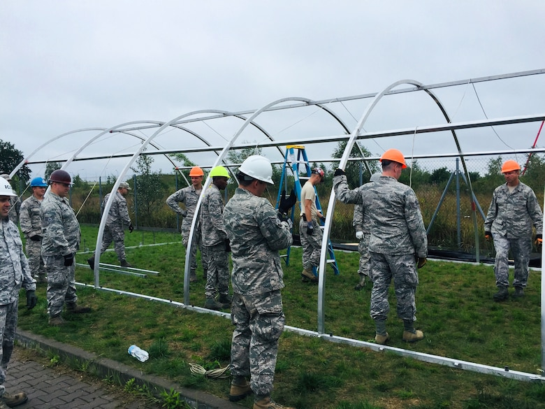 Airmen work together to setup tent city during the Deployable Air Base System (DAPS) exercise at the 31st Tactical Air Base in Poznan-Krzesiny, Poland, July 30, 2018. The DAPS exercise is a new concept for the U.S. Air Force and includes facilities, equipment, and vehicles as part of the setup to support a deployable airbase. This enables the military to respond to potential contingency needs more rapidly.