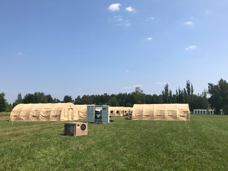 Airmen setup tent city during the Deployable Air Base System (DAPS) exercise at the 31st Tactical Air Base in Poznan-Krzesiny, Poland, July 30, 2018. The DAPS exercise is a new concept for the U.S. Air Force and includes facilities, equipment, and vehicles as part of the setup to support a deployable airbase. This enables the military to respond to potential contingency needs more rapidly.