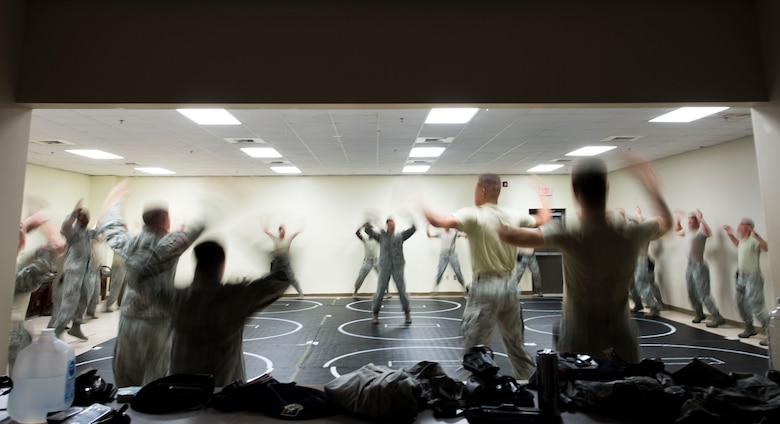 U.S. Airmen assigned to the 20th Security Forces Squadron perform jumping-jacks prior to beginning combatives training at Shaw Air Force Base, S.C., Sept. 5, 2018.