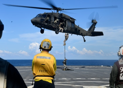U.S. and Colombian forces conduct fast rope exercises from an Army UH-60L helicopter aboard USS Gunston Hall.