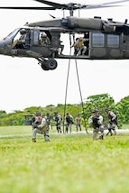U.S. and Colombian forces conduct fast rope exercises from an Army UH-60L helicopter.