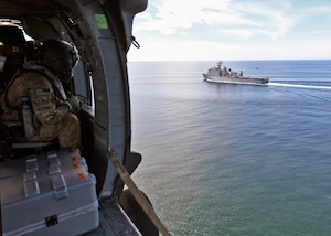 A U.S. Soldier observes USS Gunston Hall from aboard an Army UH-60L helicopter.