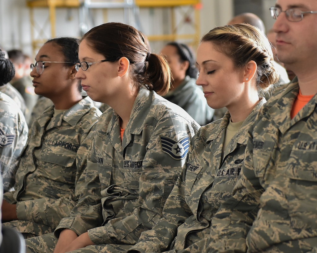 """910th Airlift Wing Reserve Citizen Airmen take a """"mindful minute"""" during a commanders call with Dr. Janelle MacAulay in Hangar 295, Youngstown Air Reserve Station, September 8, 2018. MacAulay is a wellness educator, yoga instructor, mindfulness researcher, and holds a certificate in plant based nutrition. She specializes in improving the performance of the members of high-stress organizations through a focus on nutrition, physical and mental fitness, human connection, and values discovery. (U.S. Air Force photo/Staff Sgt. Jeffrey Grossi)"""
