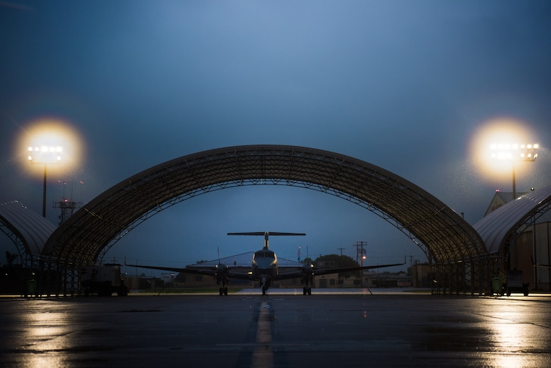 Brand new light-emitting diode, or LED, fixtures illuminate the flight line and its MC-12 Ws in an early morning downpour at Will Rogers Air National Guard Base in Oklahoma City, Sept. 7, 2018. Each pole contains 11 fixtures, which amounts to 66 fixtures on the flightline, and is part of a basewide project that replaced a total of 366 fixtures around the base. (U.S. Air National Guard Photo by Staff Sgt. Kasey M. Phipps)