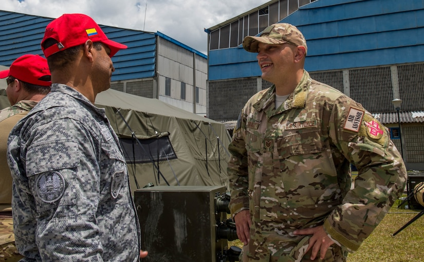 U.S. Air Force Tech. Sgt. Giacomo Zignago, right, 571st Mobility Support Advisory Squadron independent duty medical technician, speaks with a medical technician from the Colombian Air Force during the opening ceremony of Exercise Angel de los Andes, Sept. 3, 2018, at Air Combat Command-5, Rionegro, Colombia.