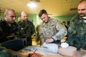 U.S. soldier teaches Bulgarian soldier how to tend a wound.