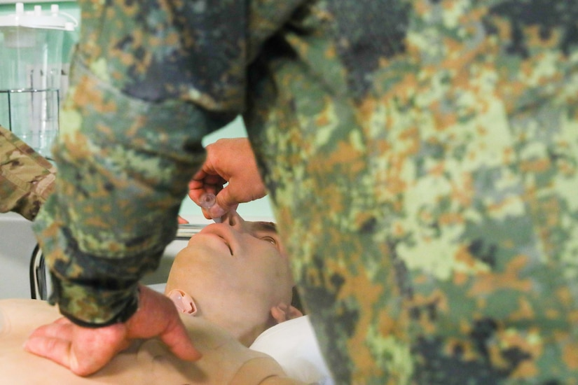 Bulgarian soldier practices combat casualty treatment on a mannequin.