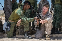 A Soldier from the Singapore Armed Forces shows U.S. Marine Corps LCpl. Dom Depuglia a Singapore Assault Rifle 21st Century during exercise Valiant Mark 2018 at Marine Corps Air-Ground Combat Center Twentynine Palms, Calif. Aug. 30, 2018