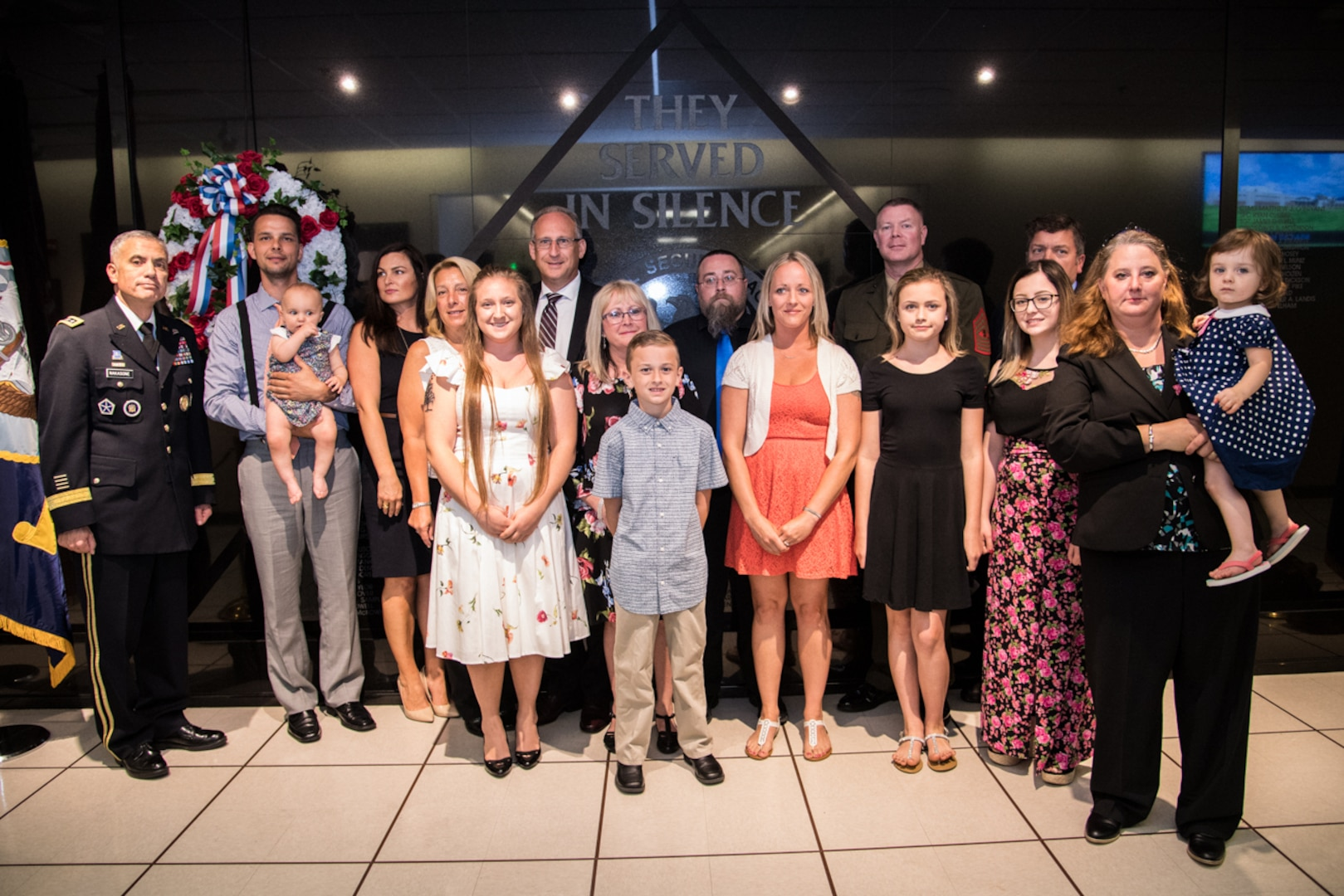 The Cavanaugh and Mitchell families stand with General Paul M. Nakasone  Director  National Security Agency in front of the Cryptologic Memorial Wall.