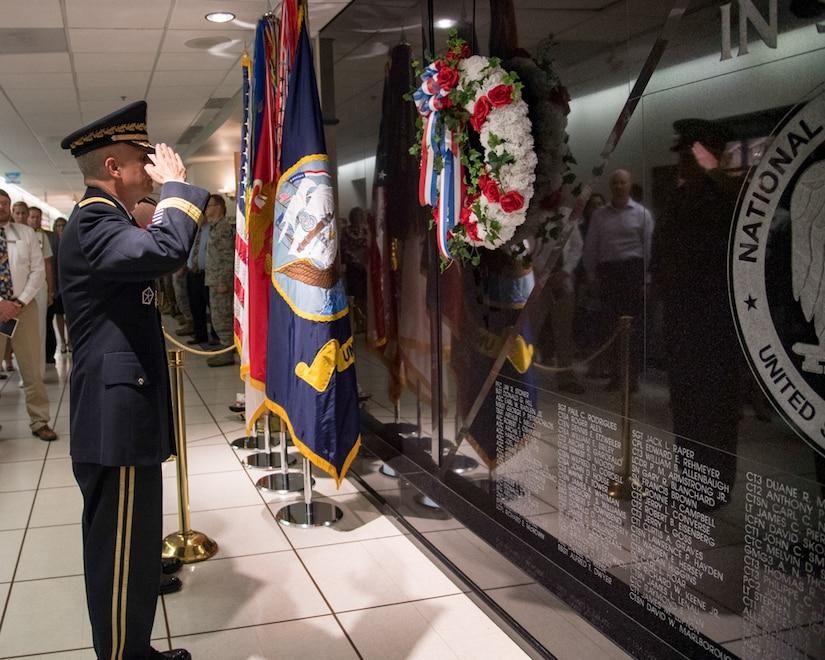 General Paul M. Nakasone  Director  National Security Agency  salutes the Memorial Wall.