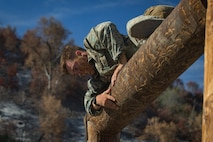 U.S. Marine Corps Lance Cpl. John Marino, a machine gunner with 1st Marine Regiment, climbs over a log during the obstacle course portion of the 1st Marine Division (MARDIV) Super Squad Competition at Marine Corps Base Camp Pendleton, California, Aug. 30, 2018.