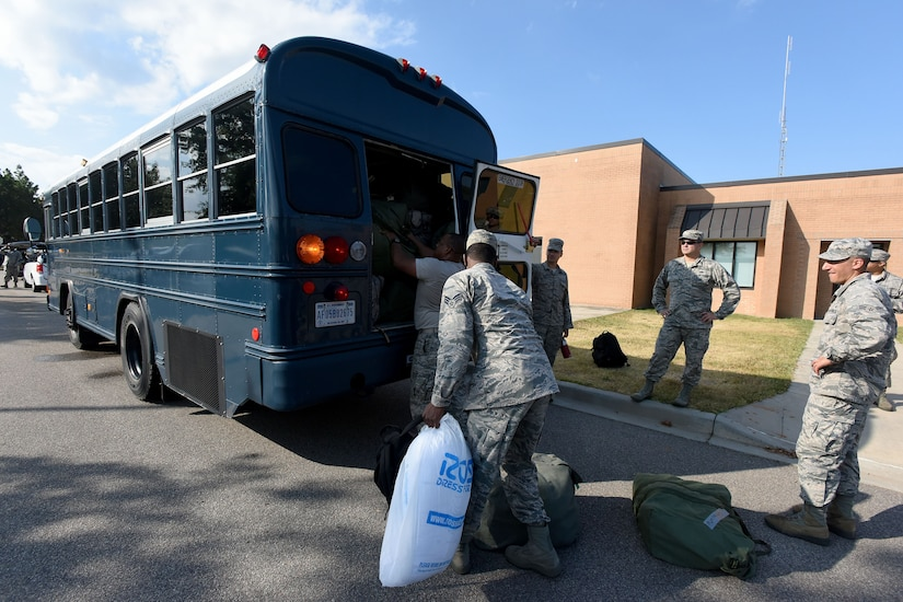 Airmen load bags of ice on the back of a bus.