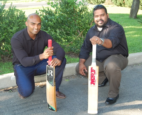 Two men, both holding their cricket bat, kneel to the ground.