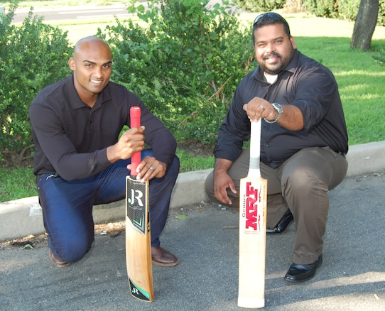 Two men, both holding cricket bats, kneel on the ground.