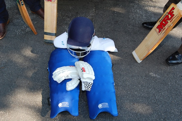 Photo of cricket equipment and uniform to include bats, helmet, gloves, and knee pads.