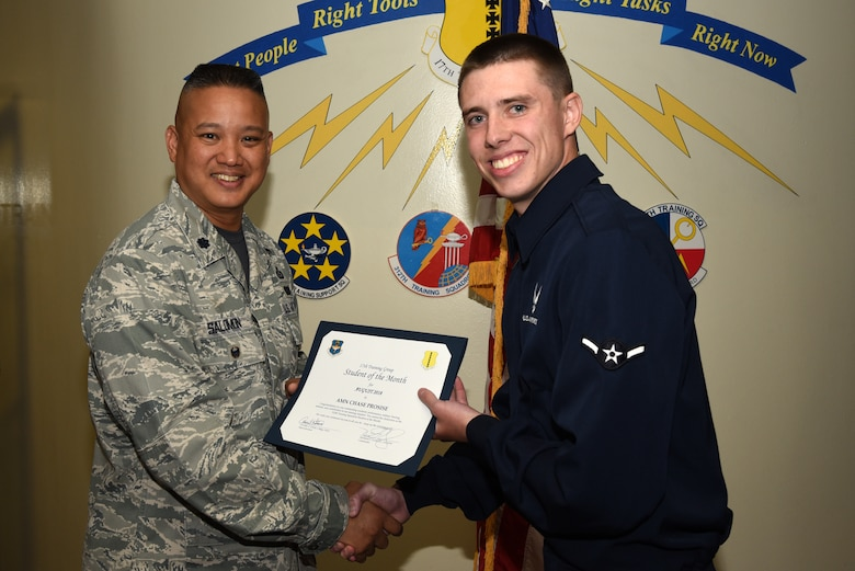 U.S. Air Force Lt. Col. Abraham Salomon, 17th Training Group deputy commander, presents the 312th Training Squadron Student of the Month award to Airman Chase Prosise, 312th TRS student, at Brandenburg Hall on Goodfellow Air Force Base, Texas, Sept. 7, 2018. The 312th TRS's mission is to provide Department of Defense and international customers with mission ready fire protection and special instruments graduates and provide mission support for the Air Force Technical Applications Center. (U.S. Air Force photo by Staff Sgt. Joshua Edwards/Released)