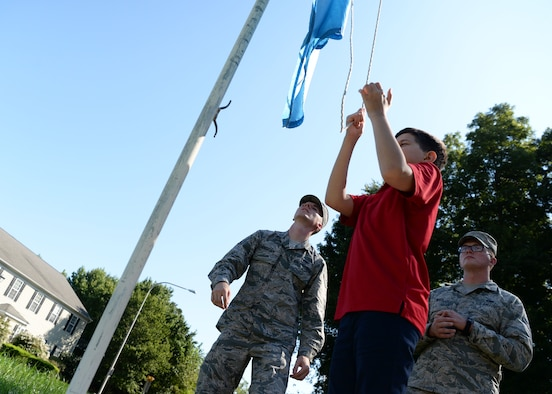 Richard Roman, seventh grade student, raises the flag Sept. 5, 2018, at St. John's Lutheran School. St. John's seventh and eighth graders took turns raising and lowering the flag to ensure they knew the proper procedures. (U.S. Air Force photo by Airman 1st Class Zoe M. Wockenfuss)