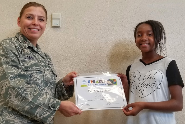 Maj. Isabella Ramirez, 90th Force Support Squadron commander, recognizes Lakayshia Thorpe, youth programs child, as the Boys & Girls Clubs of America 2018 National Arts Contest award winner for Photography, Editing and Filter Category at the F.E. Warren Air Force Base Youth Center Annex on Aug. 22, 2018. The competition's goal was to build confidence and empower youth in freedom of expression.  Thorpe's artwork will travel to regional and national conferences across the country.