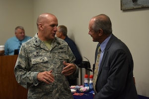 A man in the Airman Battle Uniform talks to a man in a suit.