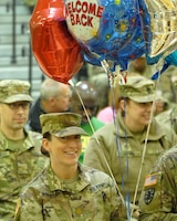 FORT KNOX, Ky - A 1st Theater Sustainment Command Soldier holds welcome home balloons for her returning Soldiers during a redeployment ceremony held here at Fort Knox. 1st TSC welcomed home 25 of its Soldiers from Kuwait at a redeployment ceremony Dec. 13 at the Sadowski Center here on post.