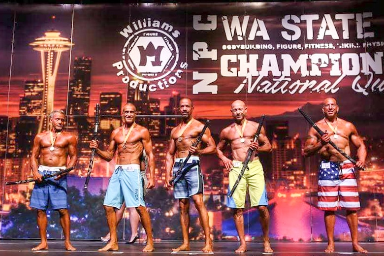 Richard Gonzales (middle), 225th Air Defense Group personnel specialist, wins first place in the Men's Physique Masters 50 & Older class at the Washington State Championship for bodybuilding at the Auburn Performing Arts Center in Auburn, Aug. 4, 2018.