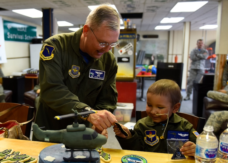 "Col. Russ Davis, 92nd Operations Group commander, presents Jimmy ""LJ"" Now with a patch and coin during his visit to the 36th Rescue Squadron Sept. 7, 2018, at Fairchild Air Force Base, Washington. During LJ's visit, Airmen from the 36th RQS pulled out all the stops, providing LJ with a flight suit with patches and his pilot wings, a personalized helmet and various other gifts to commemorate his time as an Honorary UH-1N Huey pilot. (U.S. Air Force photo/Airman 1st Class Lawrence Sena)"