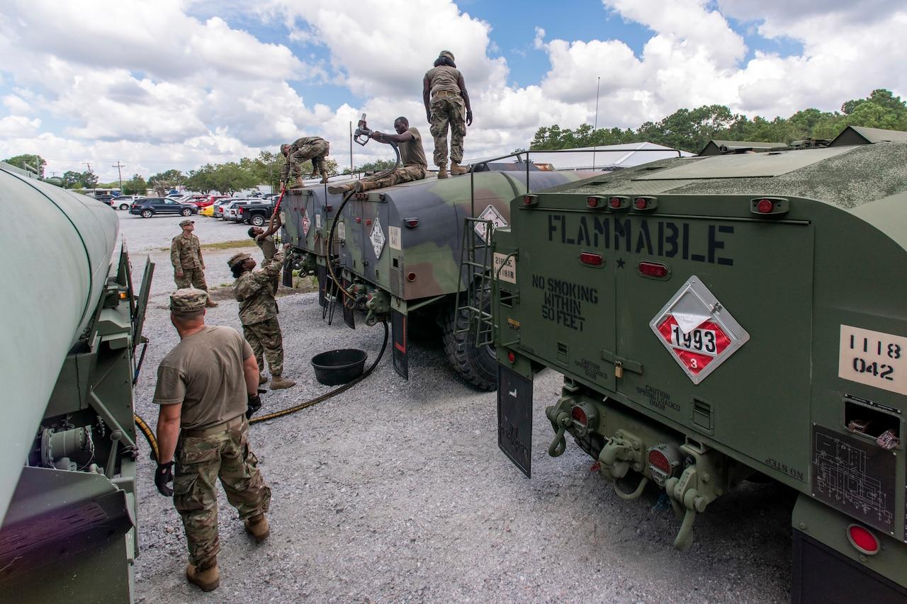 Soldiers transfer diesel fuel into tanker trucks.