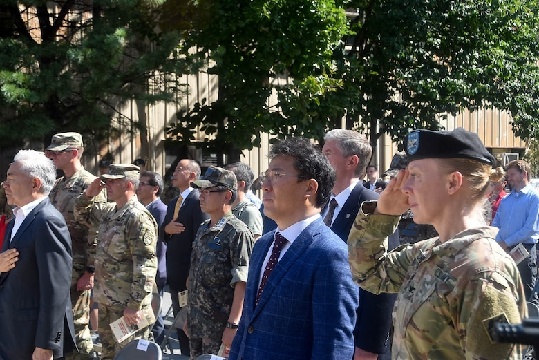 Col. Teresa Schlosser (right), U.S. Army Corps of Engineers Far East District commander, and the Honorable Seo, Yang-ho, Mayor of the Jung-gu district, honor the nation during the playing of the U.S. national anthem during a colors casing ceremony Aug. 31 to mark the closing of the district's headquarters in Seoul (Dongdaemun) and its relocation 40 miles south to Camp Humphreys.