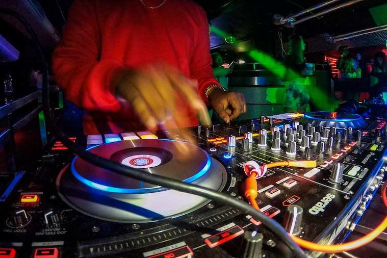 An airman spins music at a club.