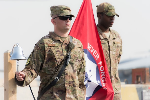 Senior Airman Adam Watson tolls a bell during a ceremony marking the 17th anniversary of the 9/11 terrorist attacks held at Al Udeid Air Base, Qatar, Sept. 11, 2018. The ceremony brought together the various emergency responder career fields represented on base to honor the sacrifices made on 9/11. (U.S. Air Force photo by Tech. Sgt. Ted Nichols/Released)