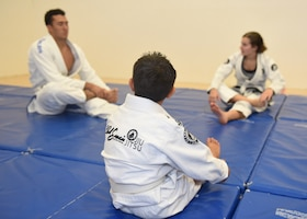 People in white uniforms practice martial arts on a  blue mat.