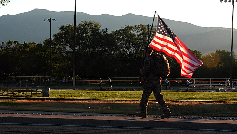 Senior Airman Samuel O'Brien with the 377th Special Forces Group carries the U.S. Flag during a ruck march commemorating the victims of the 9-11 attacks here. The march started at 6:46 a.m. (8:46 EDT, to mark the start time of when the first plane hit the twin towers 17 years ago. (U.S. Air Force photo by Jessie Perkins)