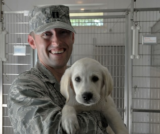 Capt. Robert C. Cost, an Intelligence team chief with the 445th Operations Support Squadron, poses with Hanson, a future service dog, at Circle Tail, Inc. in Pleasant Plain, Ohio August 13, 2018.