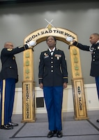 Sgt. Angela Johnson, G-6, 1st Theater Sustainment Command, walks under crossed sabers as a symbol she crossed the threshold from Soldier to noncommissioned officer during the 1st TSC induction ceremony March 2, 2018 at Fort Knox, Ky.