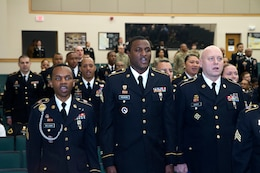 From left to right, Sgt. Nahjier Williams, a broadcast journalist with 1st Theater Sustainment Command Public Affairs, Sgt. Carlos Vaughn, G-6, 1st TSC, and Sgt. Andy Scott, material control accounting noncomissioned officer, support operations (SPO), 1st TSC, recite the NCO creed during the 1st TSC NCO induction ceremony March 2, 2018 at Fort Knox, Ky.