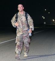 CAMP ARIFJAN, Kuwait - Sgt. 1st Class Keith Killgren, Strategic Operations and Plans (SOaP) communications noncommissioned officer in charge, 1st Theater Sustainment Command (TSC), rucks in the early morning hours during the annual Camp Arifjan Bataan Death March, Mar. 25, 2018. Killgren earned second place, finishing with a time of five hours, forty-seven minutes. (Courtesy photo, MWR)