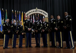 FORT KNOX, Ky. – The newest noncommissioned (NCO) inductees from the 1st Theater Sustainment Command (TSC) stand together for a group photo with Command Sgt. Major Jason Willett, senior enlisted advisor, 1st TSC, center left and keynote speaker, Sgt. Maj. Edward Bell, deputy chief of staff, G-4, center right, during the 2018 NCO Symposium, Aug 28-30, at the Gen. George Patton Museum. The symposium allowed for professional open-forum discussion amongst the NCO ranks. (U.S. Army photo by Spc. Zoran Raduka)