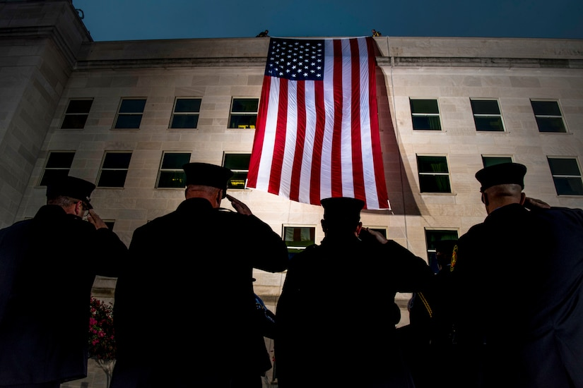 Four officers, shown from behind, salute a giant American flag on the side of the Pentagon.