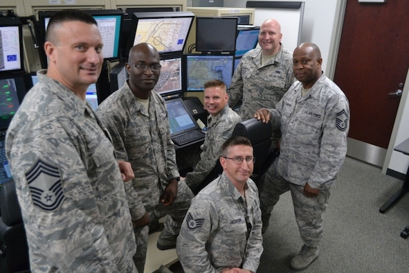 Six members of the Pennsylvania Air National Guard's 111th Operations Support Squadron stand in a room next to an MQ-9 Flight Simulator.