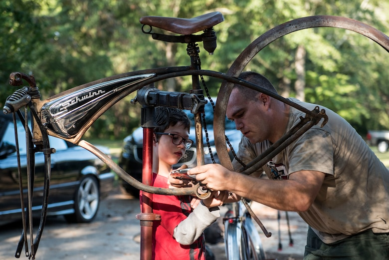 U.S. Air Force Staff Sgt. Patrick Lewis, 20th Equipment Maintenance Squadron aircraft structural maintenance mechanic, works on a bicycle with his son Evann at his home in Sumter, S.C., Sept. 10, 2018.