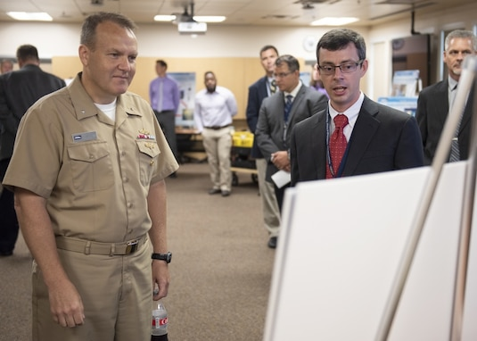 PANAMA CITY, Florida - Naval Surface Warfare Center Panama City Division (NSWC PCD) Multiple Vehicle Communications Systems Technical Direction Agent Lead Evan McCaw briefs Commander, NSWC Rear Adm. Tom Anderson, USN, about the Navy Innovative Science and Engineering Alternative Mission Packages project Sept 5, 2018. U.S. Navy photo by Ron Newsome