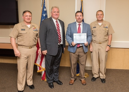 PANAMA CITY, Florida - Randall Whitehead is presented the Warfare Center United States Marine Corps Collaboration Team Award by Commander, Naval Surface Warfare Center Rear Adm. Tom Anderson, USN, Sept. 6, 2018. Pictured from left to right: NSWC Panama City Division (PCD) Commanding Officer Capt. Aaron Peters, USN, NSWC PCD Technical Director Ed Stewart (SES), Randall Whitehead, Rear Adm. Tom Anderson, USN. U.S. Navy photo by Anthony Powers