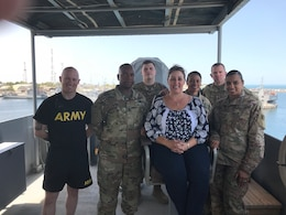 KUWAIT NAVAL BASE, Kuwait - – Theresa Scott, family readiness support assistant, 1st Theater Sustainment Command (TSC), middle, poses with several 1st TSC Soldiers while onboard an Army Landing Support Vessel, June 16. Scott traveled to Camp Arifjan to experience life as a Soldier on deployment.