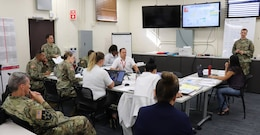 Honolulu District Commander Lt. Col. Kathryn Sanborn (center, left) met with Emergency Operation Center (EOC) personnel Sept. 11, 2018, discussing the latest updates to the USACE response to Typhoon Mangkhut that ravaged the Commonwealth of the Northern Mariana Islands, and Tropical Storm Olivia that is expected to make landfall tonight in the eastern Hawaiian Islands.