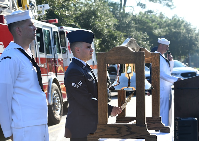 U.S. Air Force Senior Airman Zachary Slater, 81st Infrastructure Division firefighter, rings a tribute bell as Chief Aviation Electronics Technician (Select) Adrian Pineiro, The Center for Naval Aviation Technical Training Unit student, stands by during a 9/11 ceremony in front of the 81st Training Wing headquarters building at Keesler Air Force Base, Mississippi, Sept. 11, 2018. Seventeen years ago on Sept. 11, 2001, 19 terrorists simultaneously hijacked four passenger jets; flying one into the Pentagon and two into the World Trade Center in New York City, New York, and one crashing outside of Shanksville, Pennsylvania. A total of 2,996 people were killed in the attacks. (U.S. Air Force photo by Kemberly Groue)