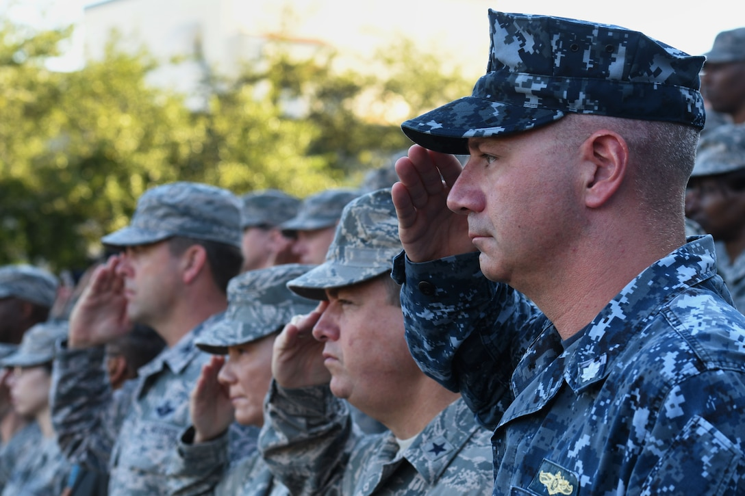 U.S. Navy Cmdr. Timothy Knapp, Center for Naval Aviation Technical Training Unit Keesler commanding officer, and other Keesler leadership render a salute during a 9/11 ceremony in front of the 81st Training Wing headquarters building at Keesler Air Force Base, Mississippi, Sept. 11, 2018. The event honored those who lost their lives during the 9/11 attacks. (U.S. Air Force photo by Kemberly Groue)