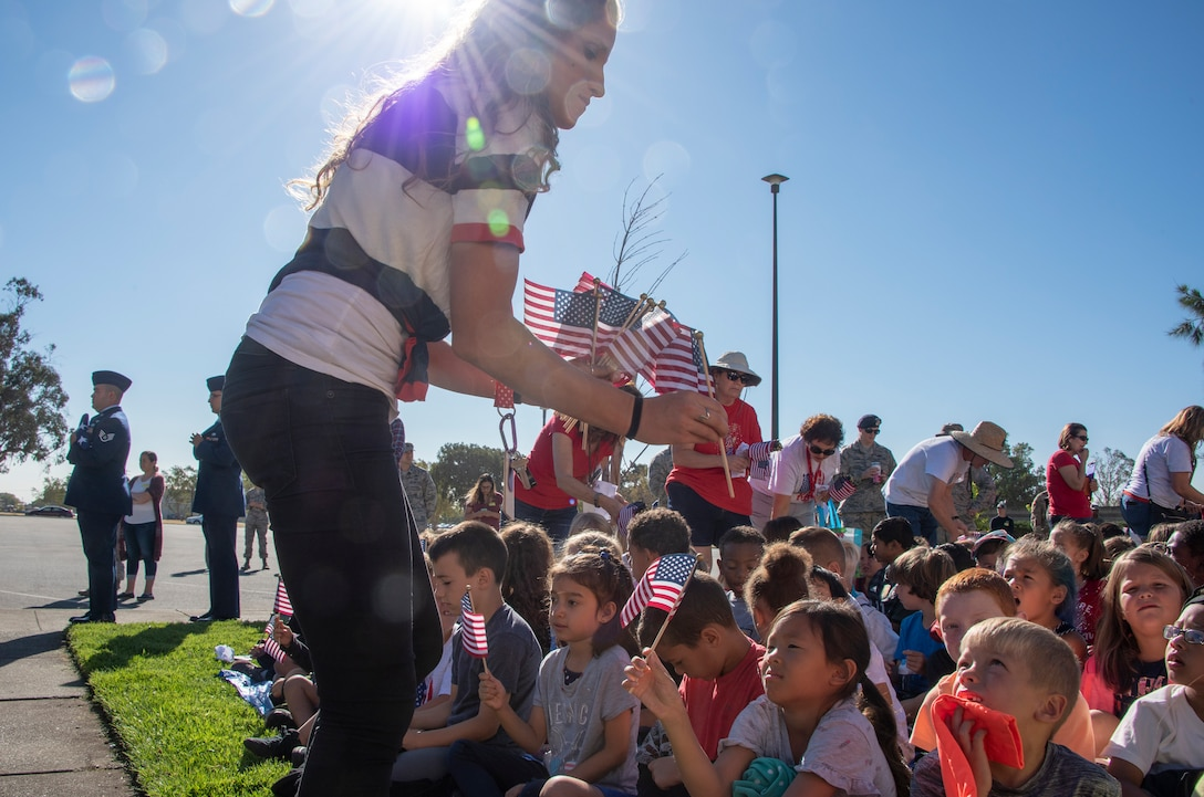 American Flags are handed out to children attending the Remembrance Day Freedom Walk, Sep. 11, 2018, at Travis Air Force Base, Calif. The walk commemorates those who lost their lives on 9/11. (U.S. Air Force Photo by Heide Couch)