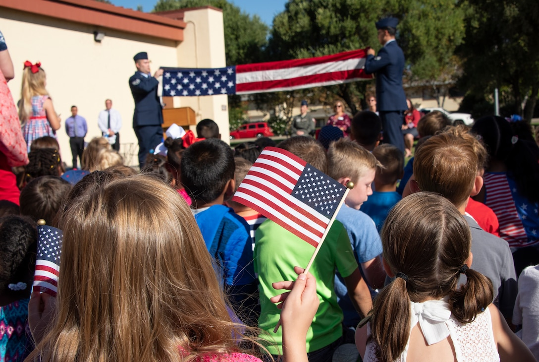 Children watch the Travis Honor Guard performing the flag folding ceremony during the Remembrance Day Freedom Walk, Sep. 11, 2018, at Travis Air Force Base, Calif. The walk commemorates those who lost their lives on 9/11. (U.S. Air Force Photo by Heide Couch)