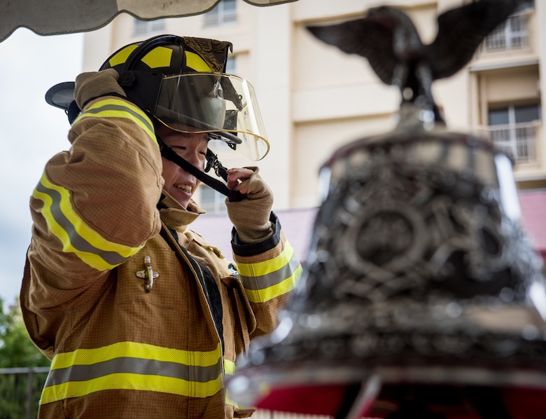 A Japanese Firefighter dons a fire helmet