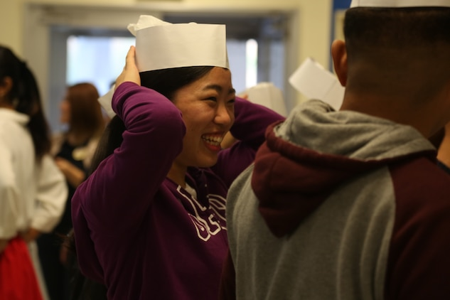 CAMP COURTNEY, OKINAWA, Japan – A high school student from the local community laughs while putting on a cook's hat during Camp Courtney's Summer English class Aug. 16 at the Camp Courtney Mess Hall, Okinawa, Japan.